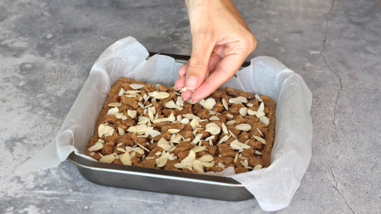 Ricoprite la base con la marmellata e il rimanente impasto raffreddato, sbriciolandolo con le dita. Cospargete quindi con le mandorle a lamelle e cuocete in forno per 25 minuti.