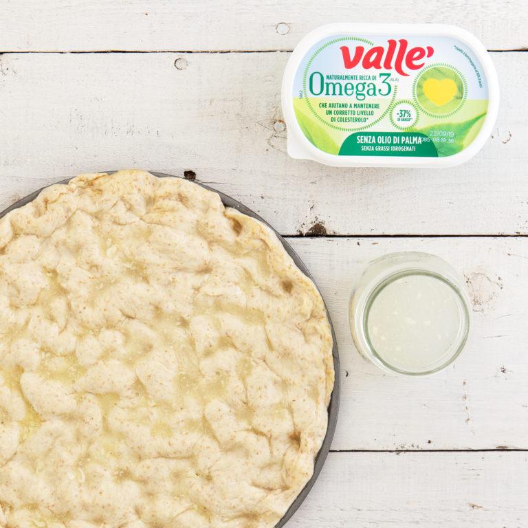 Con le dita creare dei buchi sulla teglia, preparare un'emulsione di acqua, 20 gr di Vallè Omega 3 e spargere sopra.
