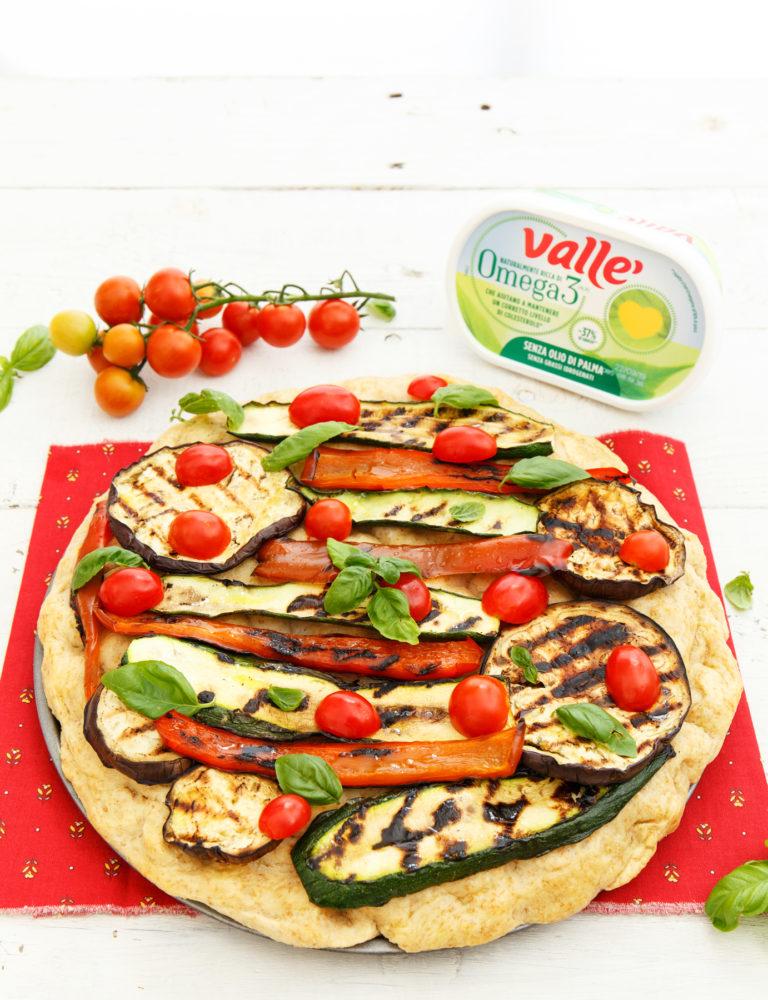 Infornare per 20 minuti, tirate fuori la focaccia e farcirla con le verdure grigliate prima di infornare per altri 10 minuti. Sfornare e lasciare intiepidire prima di aggiungere pomodorini e basilico fresco.