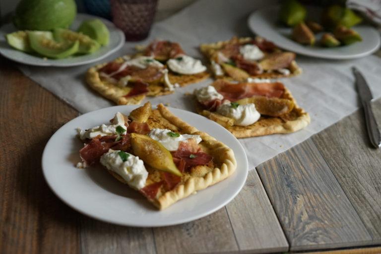Completare con il prosciutto, un filo d'olio e foglie di basilico e gustare la pizza.