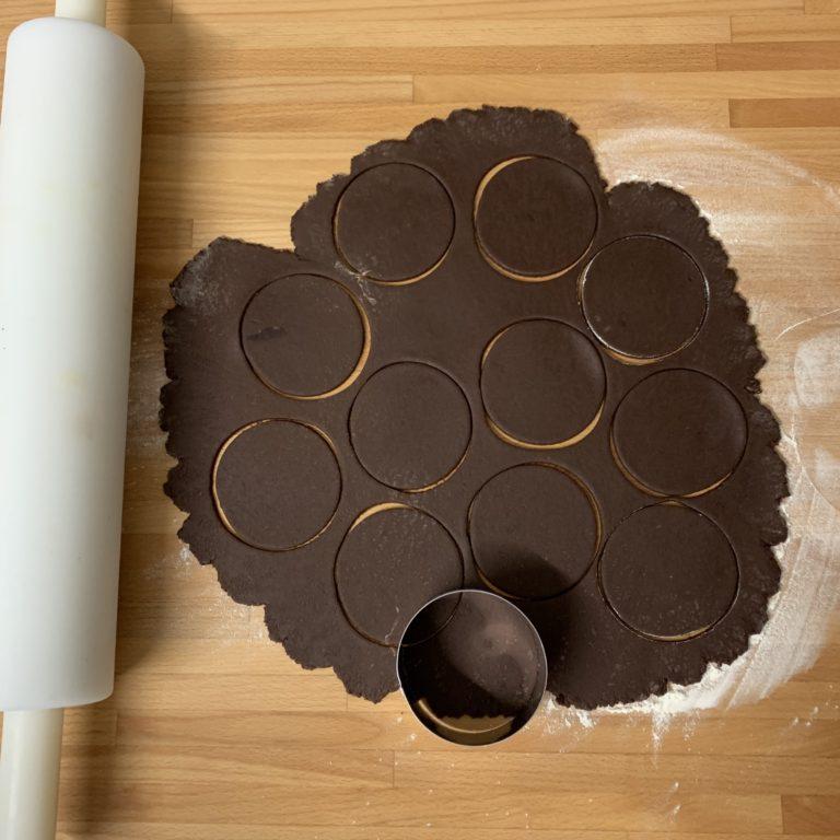 Stendiamo con un mattarello la pasta frolla al cacao, abbastanza sottile, coppiamo con un coppa-pasta rotondo i nostri biscotti, foriamo con una forchetta la superficie e sistemiamo su teglia con carta da forno.