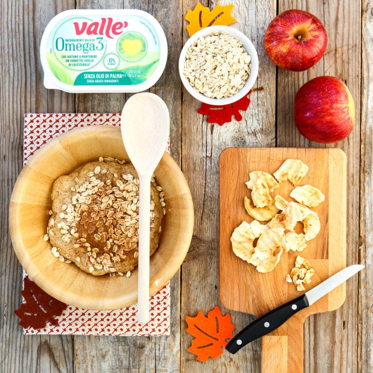 Tagliare le mele disidratate a tocchetti, con l'aiuto di un cucchiaio di legno aggiungere all'impasto con la noce moscata e i fiocchi d'avena.