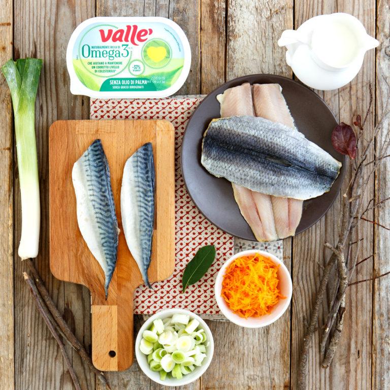 Preparare il filetto di sgombro e di aringa, togliere la pelle e tagliare a tocchetti, ridurre il porro a rondelle, la carota tritata finemente, il latte e l'alloro.