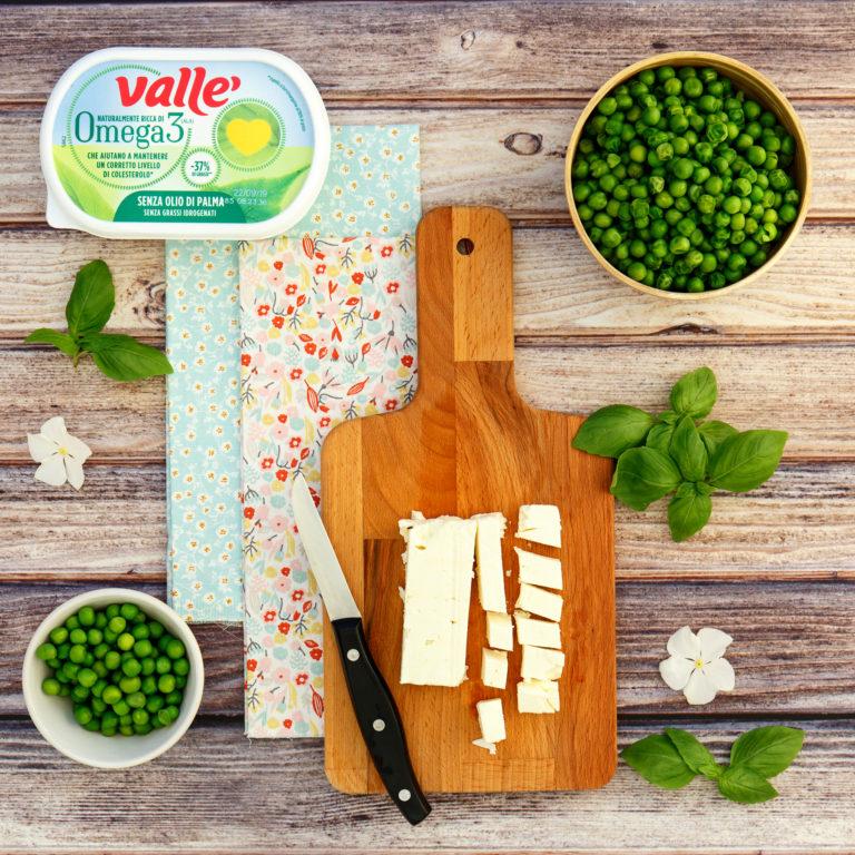 Cuocere i piselli in abbondate acqua salata e tagliare la feta a piccoli tocchetti, lavare e asciugare le foglie di basilico.