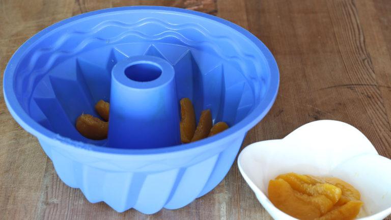 Tagliate le pesche a fette sottili e disponetele a raggiera sul fondo di uno stampo da ciambella di 22 o 24 cm di diametro.