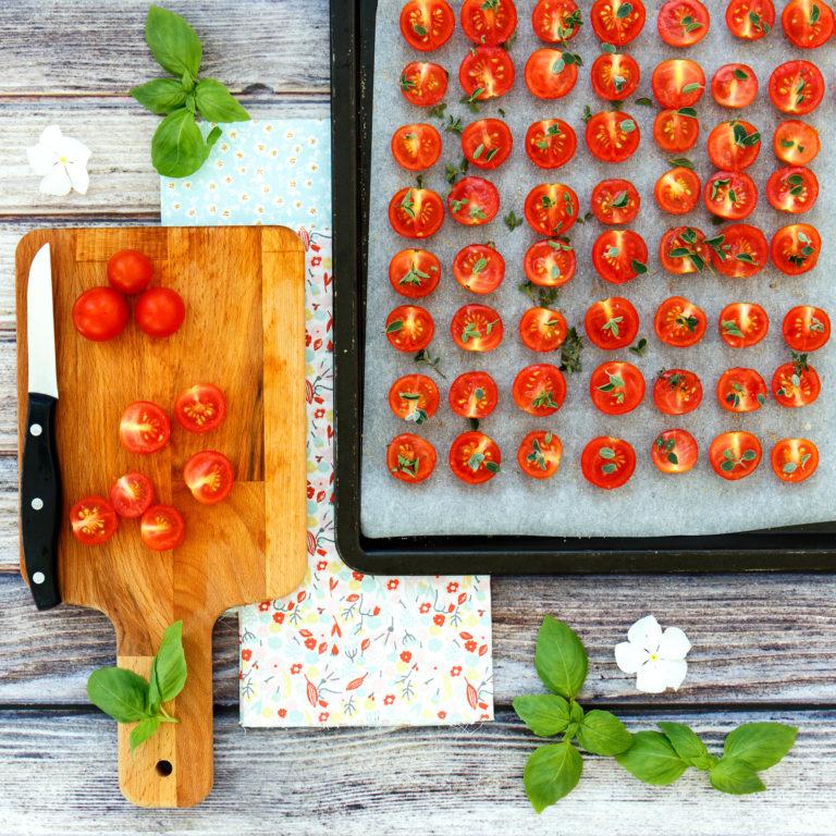 Tagliare i pomodorini a metà e posizionarli su carta da forno vicini uno all'altro fino a riempire la teglia, spolverizzarli con dello zucchero, un pizzico di sale e il timo. Infornare a 140°-150° per un'ora e mezza circa, i pomodorini dovranno asciugarsi ed appassire.