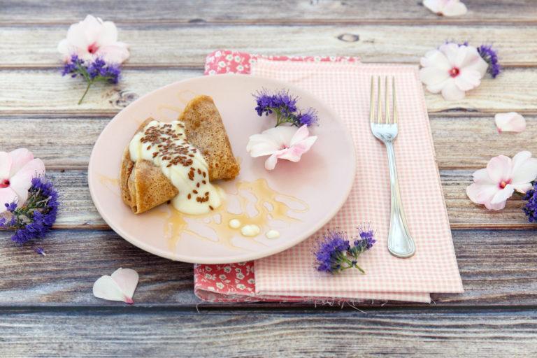 Servire le mini- crêpe ripiegate e accompagnate da un cucchiaio di yogurt vegetale alla mandorla, un tocco di miele e i semi di lino.