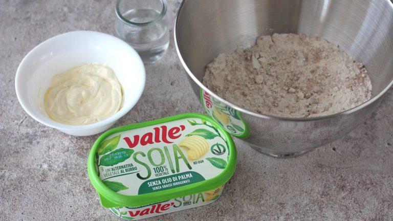 Unite in una ciotola (o nella planetaria) gli ingredienti secchi ovvero farina integrale, cacao, zucchero, bicarbonato e sale. A parte preparate l'acqua e fate ammorbidire Vallé Soia.