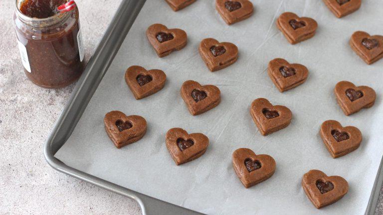 Allineate metà dei biscotti su una teglia ampia ricoperta di carta forno. Mescolate la marmellata di fichi con la scorza di limone grattugiata e mettetene un cucchiaino scarso al centro di ogni biscotto. Ricoprite i biscotti con l'altra metà e premete leggermente i bordi per chiudere la marmellata all'interno. Cuocete a 180°C per 12 minuti.