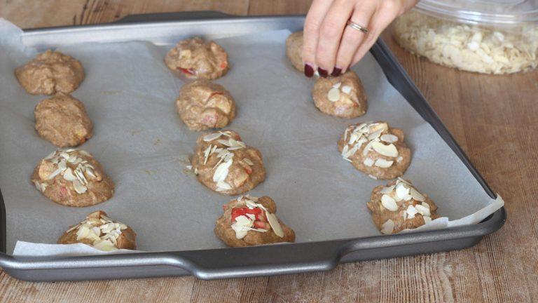 Preparate una teglia ampia ricoprendola di carta forno, formate i biscotti direttamente sulla teglia aiutandovi con due cucchiai leggermente inumiditi d'acqua. Cospargete la superficie con le mandorle a lamelle.