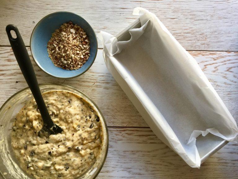 Versare il composto in uno stampo per plum cake rivestito con carta da forno e distribuire sulla superficie la granella di noci e mandorle.