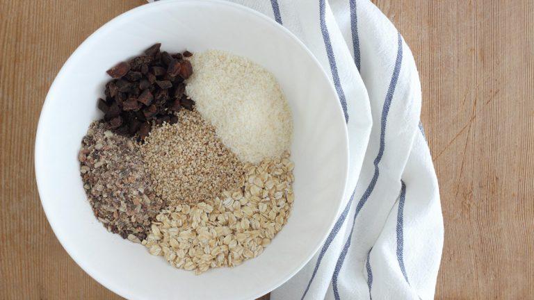 Tritate grossolanamente nel mixer i semi di zucca, quelli di girasole e le mandorle. Metteteli in una ciotola insieme ai fiocchi di avena, la farina di cocco, il bicarbonato e i mirtilli essiccati.