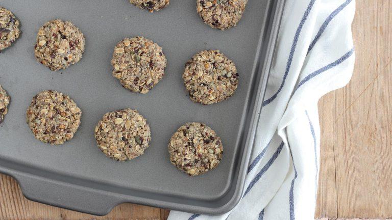 Accendete il forno a 180°C. Formate i cookies prelevando palline di impasto grandi come una grossa noce, appiattiteli leggermente fino allo spessore di mezzo centimetro e adagiateli via via su una teglia da forno antiaderente.
