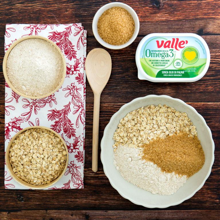 In una ciotola miscelare la farina di farro integrale, con lievito, fiocchi d'avena, zucchero di canna e il pizzico di sale