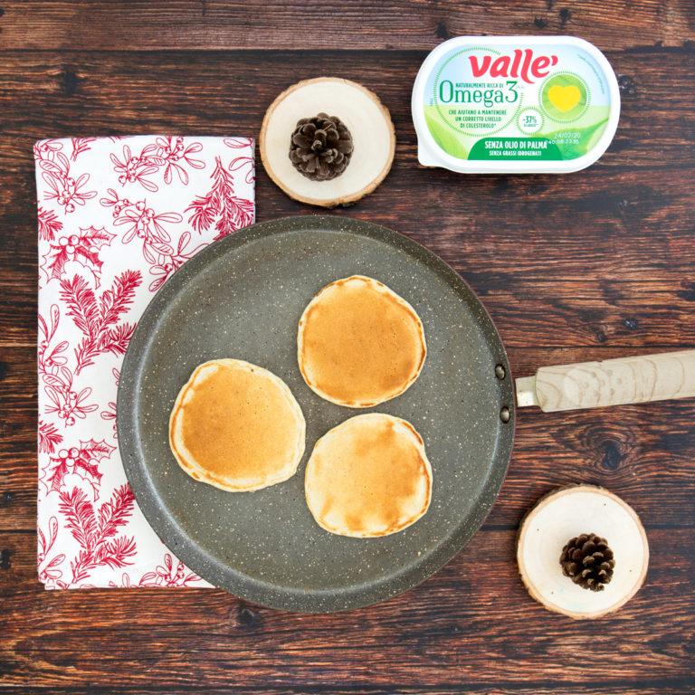 Scaldare una pentola antiaderente leggermente unta con Vallé Omega3, prendere il composto con l'aiuto di un piccolo mestolo e formare il pancake. Lasciare cuocere un paio di minuti fino a quando si formeranno delle bolle superficie: a quel punto girare e proseguire la cottura anche sull'altro lato prima di toglierlo e disporlo su un piatto. Proseguire nello stesso modo anche con gli altri pancake.