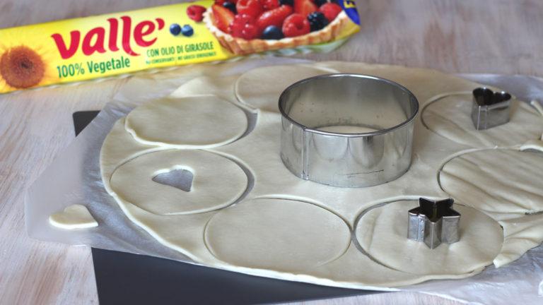 Nel frattempo accendete il forno a 200°C. Ricavate dalla frolla dodici dischi di uguale dimensione, usando un coppapasta o un bicchiere di circa 6 cm di diametro. Praticate su sei dischi un foro al centro usando delle formine, oppure fate un taglio a croce con un coltello.