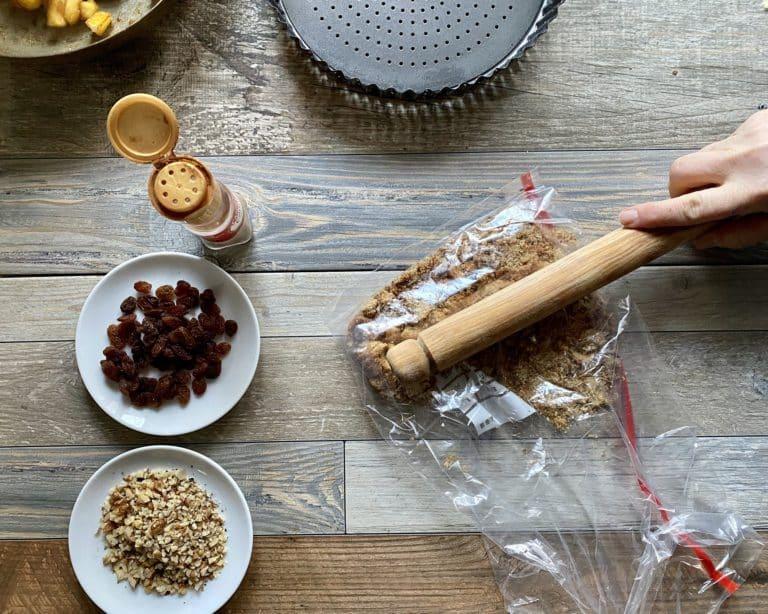 Con un mattarello sbriciolare grossolanamente i biscotti e aggiungerli alle mele con l'uvetta, le noci e la cannella