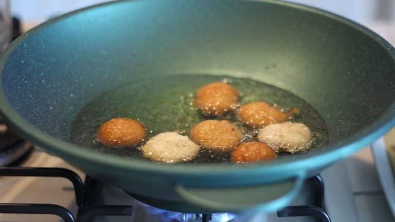 Scaldate in una padella ampia dell'olio di arachidi e portatelo a 180°C. Create le frittelle aiutandovi con due cucchiaini: dovrete formare delle piccole quenelles e farle scivolare nell'olio delicatamente. Cuocetene 6 o 7 per volta per circa 2 minuti, poi giratele e cuocetele dall'altro lato