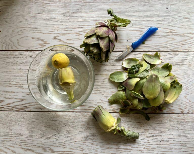 Pulire i carciofi eliminando le foglie più dure e immergerli in acqua acidulata con limone