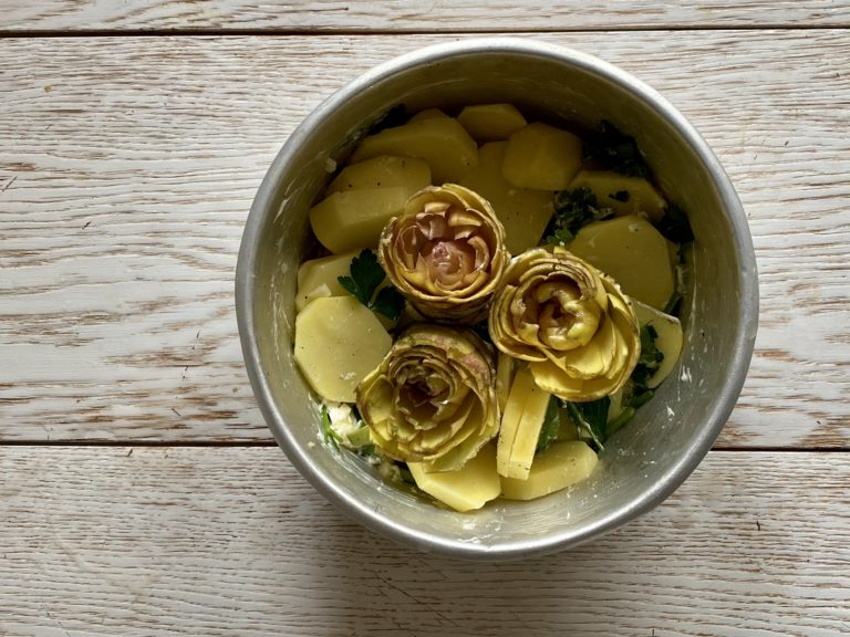 Aprire a fiore i carciofi e incastrarli tra le patate in modo da farli rimanere in piedi