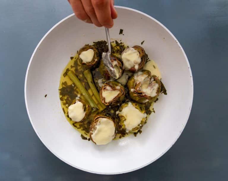 Tagliare il taleggio a cubetti e scioglierlo con l'alternativa vegetale alla panna in un pentolino con un leccapentole a fuoco dolce. Versare la fonduta di taleggio dentro i carciofi. Infornarli a 160° per 15 minuti. Serviteli irrorandoli con il sugo di cottura
