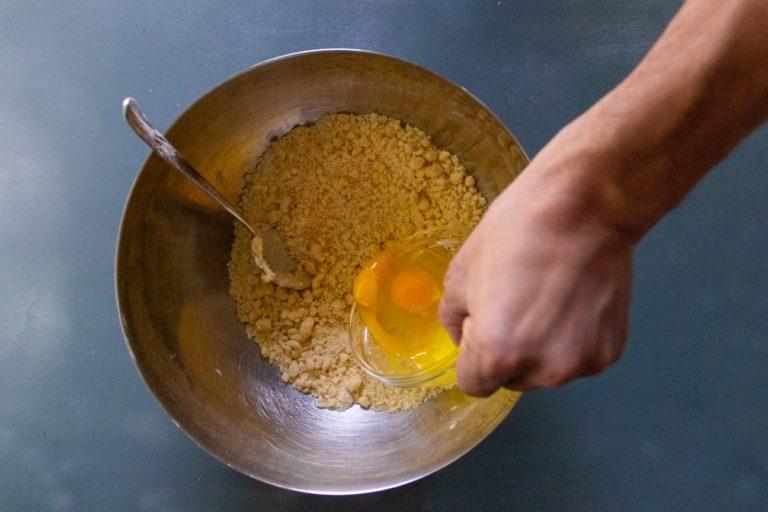Aggiungere un uovo intero ed un tuorlo, impastare fino a che l'impasto non abbia preso forma (massimo 2 minuti)