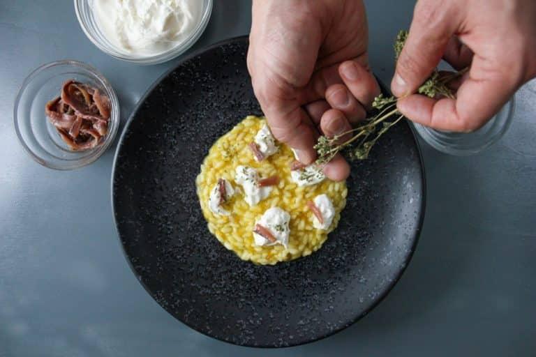 Impiattare il riso ultimando con burrata, pepe, acciughe e origano in polvere