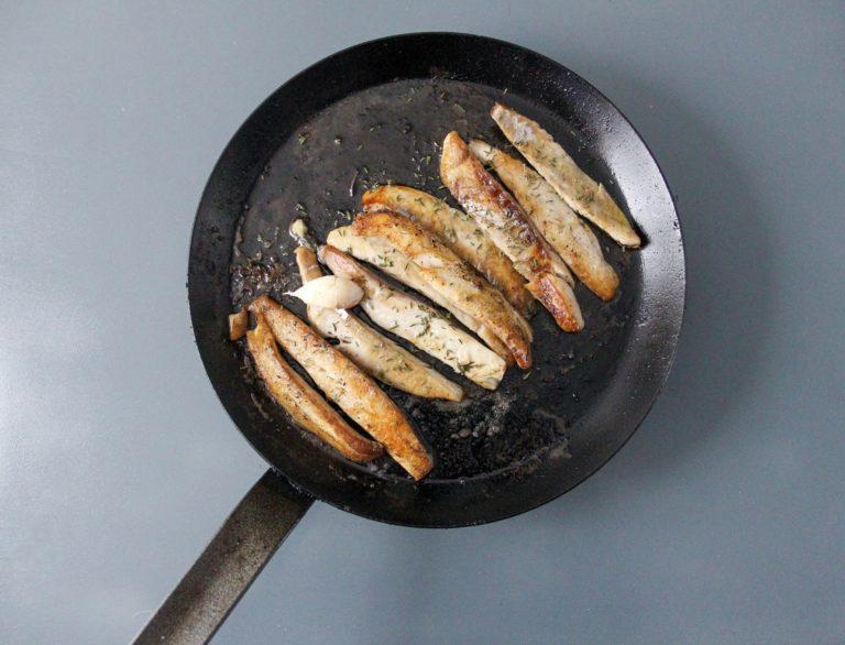 Nel frattempo far sciogliere 100 g di Vallé Naturalmente in una pentola antiaderente con uno spicchio d'aglio. Aggiungere il timo sfogliato e arrostire a fuoco vivace i filetti di pesce per 2 minuti dal primo lato. Girare e proseguire per 30 secondi