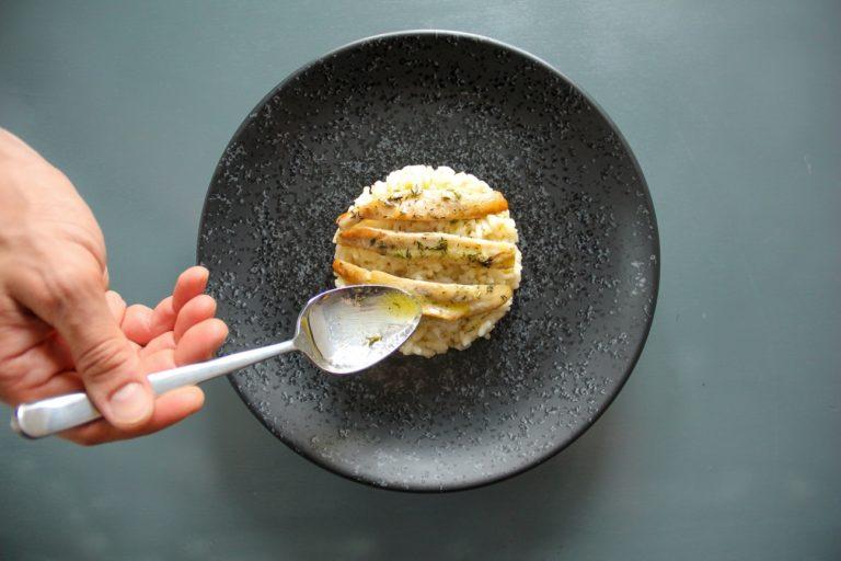 Impiattare adagiando i filetti di pesce sopra il risotto, irrorare con Vallé Naturalmente e timo