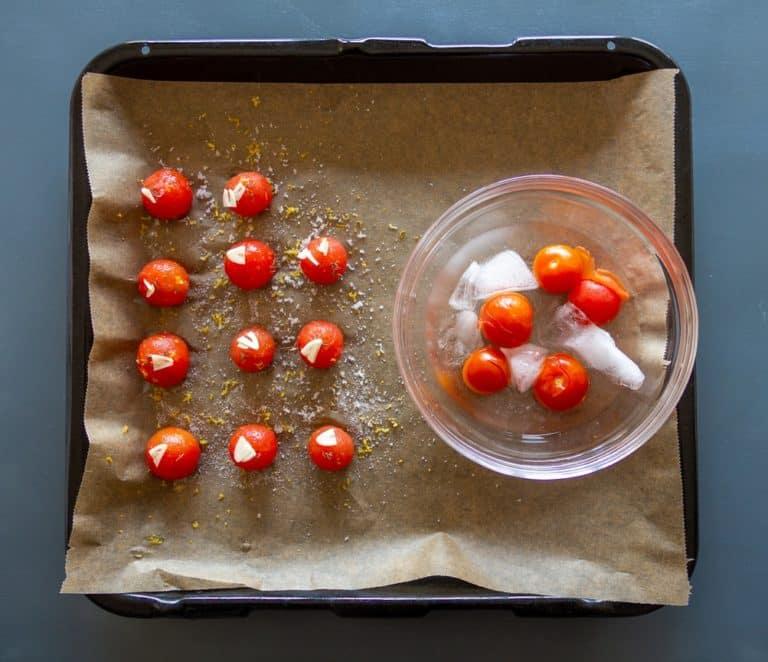 """Sbollentare i pomodori per 20 secondi facendo un'incisione ad """"X"""" sul dorso del pomodoro. Dopodiché raffreddare in acqua e ghiaccio. Disporre su di una teglia con carta da forno, salare e zuccherare ed aggiungere gli aromi: timo, aglio e scorza di limone. Cuocere a 140° per un'ora in forno ventilato"""