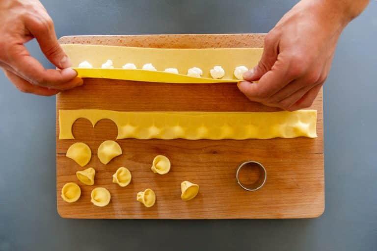 Stendere la pasta fresca ad un millimetro di spessore con l'aiuto di una macchina per la pasta e fare i tortelli aiutandovi con un coppa pasta, avendo cura di usare la semola durante la lavorazione per evitare che si attacchino