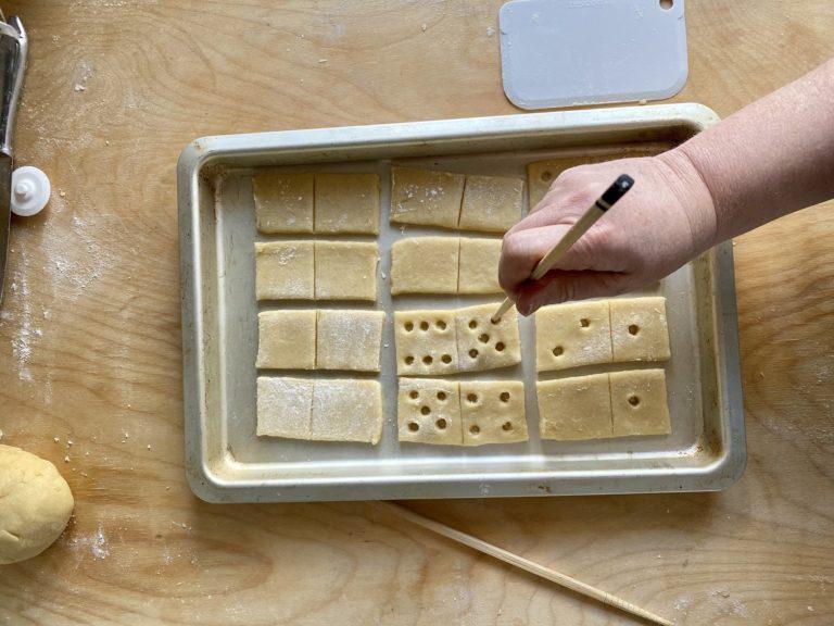 Aiutandosi con una bacchetta di legno fare dei buchi come i pallini del gioco del domino, sulla metà dei rettangoli di frolla
