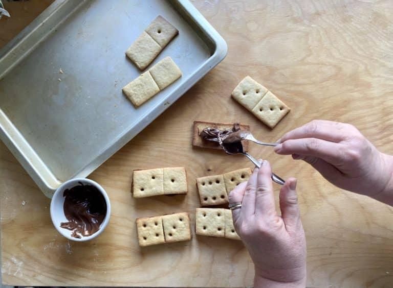 Cuocere in forno a 180° per 15 minuti circa, facendo attenzione a non far scurire troppo la frolla. Far raffreddare. Spalmare la crema di nocciole sulle strisce intere e sovrapporre quelle con i buchi