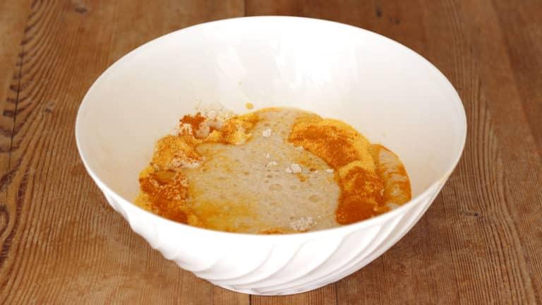 Unite in una ciotola le farine con la curcuma, versate al centro il lievito sciolto ed iniziate ad impastare