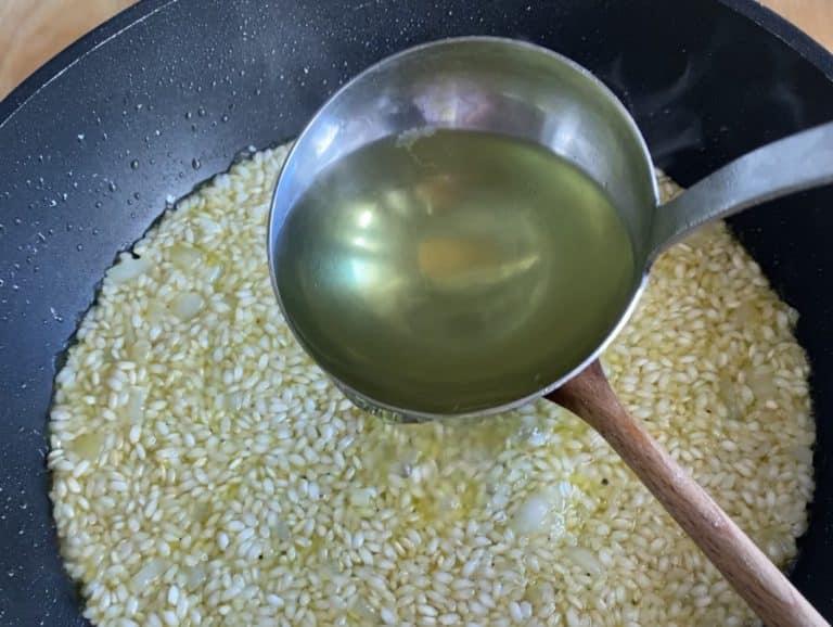 Versare un mestolo di brodo vegetale bollente e mescolare. Continuare ad aggiungerlo appena viene assorbito il precedente