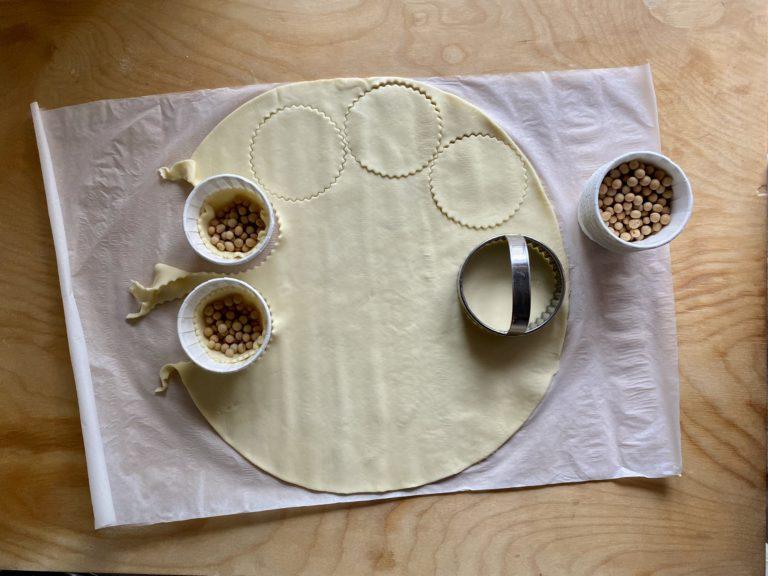 Sistemare ciascun cerchio di brisé in un pirottino per muffin e riempire la base di legumi secchi