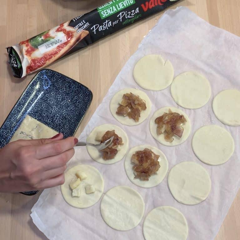 Farciamo la superficie di ogni pizzetta con qualche cubetto di gorgonzola, un cucchiaino di cipolle caramellate