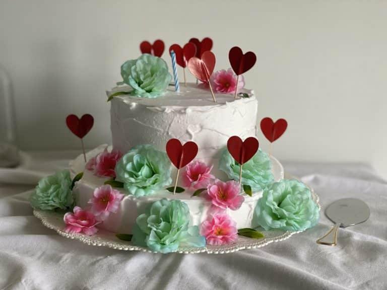 Distribuire uno strato di panna e sovrapporre i dischi. Quindi decorare la torta con panna,  fiori e cuori.