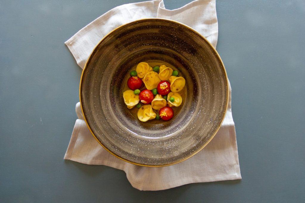 Tortelli ripieni di ricotta di pecora, pomodori canditi, piselli