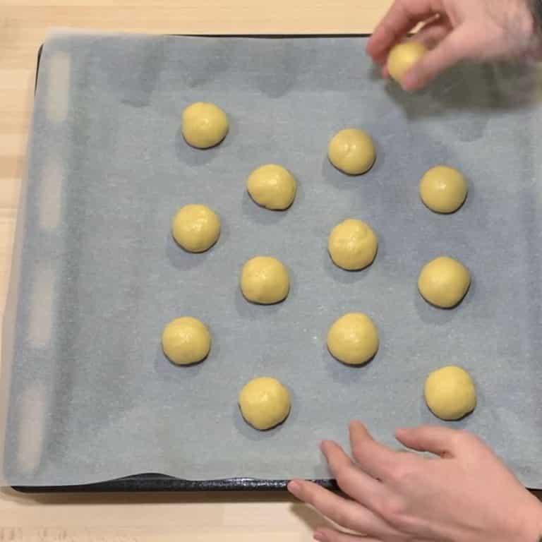 Intanto prepariamo la ganache sciogliendo il cioccolato tritato nella panna bollente. Prepariamo anche la bagna miscelando l'alchermes con l'acqua. Prendiamo il nostro impasto, formiamo delle palline grandi come noci e sistemiamole su teglia rivestita con carta forno. Cuociamo in forno preriscaldato a 170°C per circa 15-20 minuti o finchè saranno belle dorate
