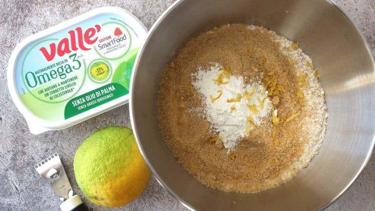 Unite in una ciotola (o in planetaria) la farina integrale, lo zucchero, il lievito, il sale e la scorza di limone