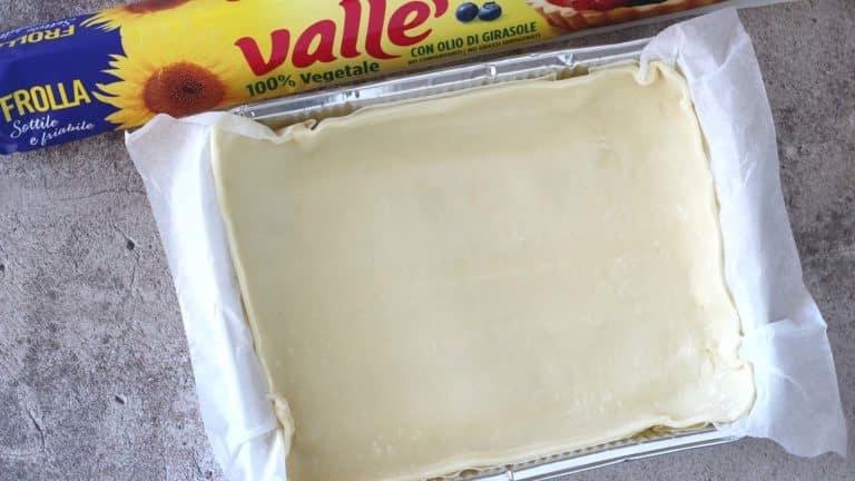 Foderate il fondo di uno stampo rettangolare da 20x15 cm con la frolla Vallé, avendo cura di creare anche un bordo alto circa 1 centimetro. Tenete da parte i ritagli, che vi serviranno per creare la copertura della torta