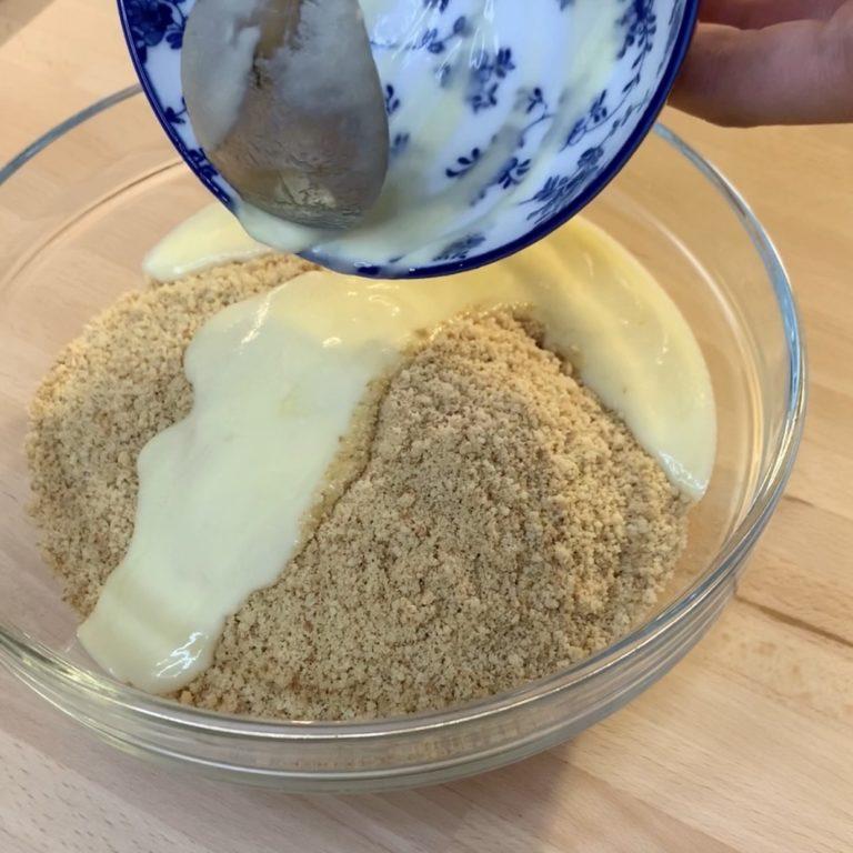 Tritiamo i biscotti al mixer ed uniamo al burro fuso. Stendiamo nella teglia e schiacciamo bene con il dorso di un cucchiaio, e poniamo in frigorifero mentre prepariamo la crema della cheesecake