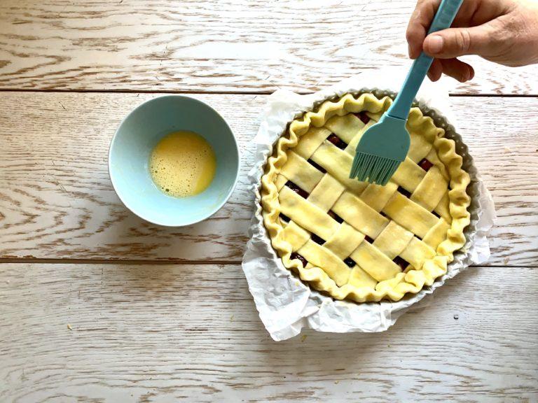 Spennellare il tuorlo d'uovo sbattuto e distribuire in superficie il cucchiaio di zucchero