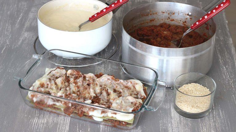 Accendete il forno a 220°C. Prendete una pirofila e mettete sul fondo due cucchiai di ragù di melanzane e uno di besciamella, mescolateli e ricopriteli con le sfoglie per lasagne. Proseguite gli strati mettendo nell'ordine sugo, besciamella, lievito alimentare, basilico e le sfoglie. Terminate con il lievito alimentare.<br />