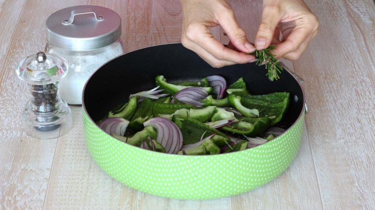 Tagliate i peperoni in falde e la cipolla a fette spesse 3-4 mm. Disponete le verdure sul fondo dello stampo, i peperoni con la pelle verso il basso. Cospargete con sale, pepe, timo e rosmarino a piacere quindi cuocete in forno per 20 minuti.
