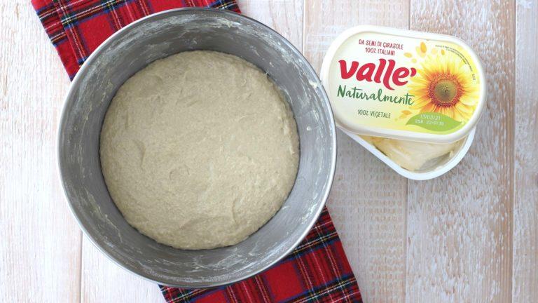 Riprendete l'impasto e lavoratelo, per smontare la lievitazione. Aggiungete la farina, lo zucchero, il sale, la vaniglia e la scorza d'arancia, il lievito sciolto nel latte ed impastate. Aggiungete quindi Vallé Naturalmente sciolta e lavorate l'impasto fino a farla incorporare completamente.
