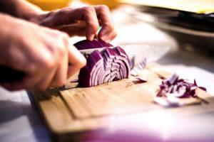 Frutta e verdura viola e blu mani che tagliano cipolla