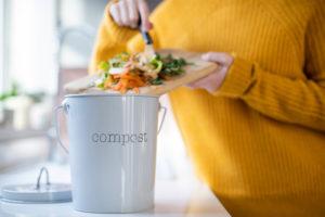 compost-fai-da-te-ragazza-con-maglione-giallo-che-versa-bucce-in-un-cestino-per-il-compost-da-tagliere-di-legno