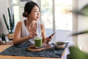 tè matcha ragazza che mescola nel bicchiere seduta al tavolo con telefono